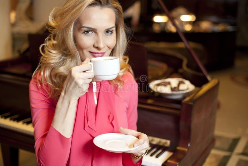 美丽的女孩饮用的咖啡 免版税库存照片