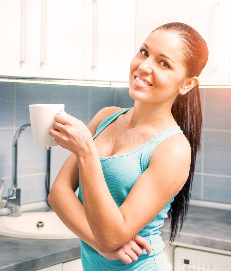 美丽的女孩饮用的茶在厨房里 库存图片