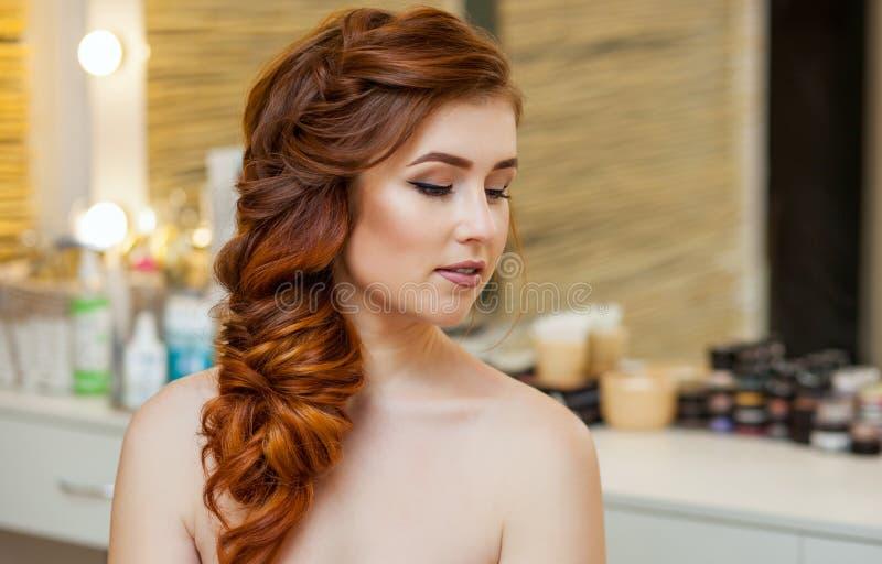 美丽的女孩,有长期的,红发长毛 美发师编织法国辫子,在美容院的特写镜头 库存图片