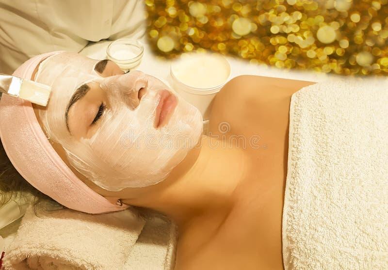 美丽的女孩,面具化妆专业美容师健康在温泉沙龙润肤霜skincare整容术,放松年轻人 库存照片