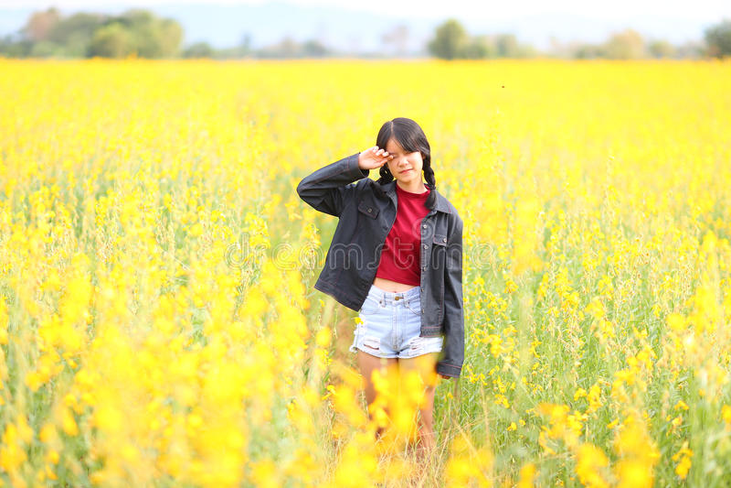 美丽的女孩,晴朗的夏天的画象有黄色花的 图库摄影