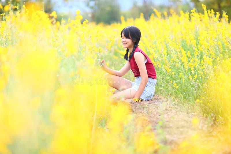 美丽的女孩,晴朗的夏天的画象有黄色花的 免版税图库摄影