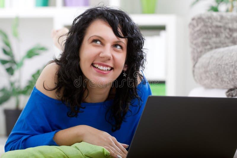 美丽的女孩画象在家有笔记本的 免版税库存照片