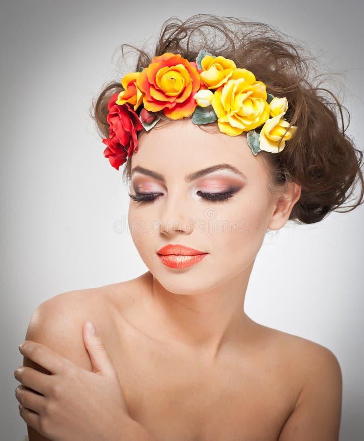美丽的女孩画象在有红色和黄色玫瑰的演播室在她的头发和赤裸肩膀 有构成的性感的少妇 免版税库存照片