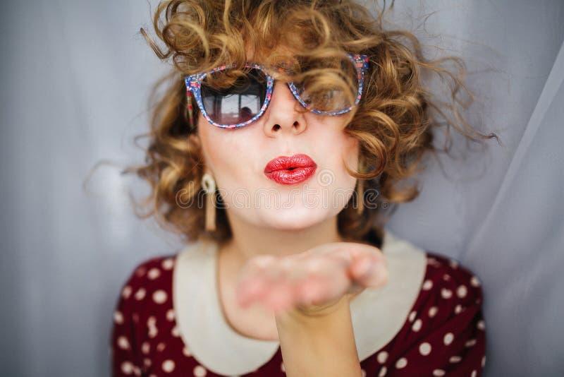 美丽的女孩画象有红色嘴唇和减速火箭的太阳镜的 免版税库存图片