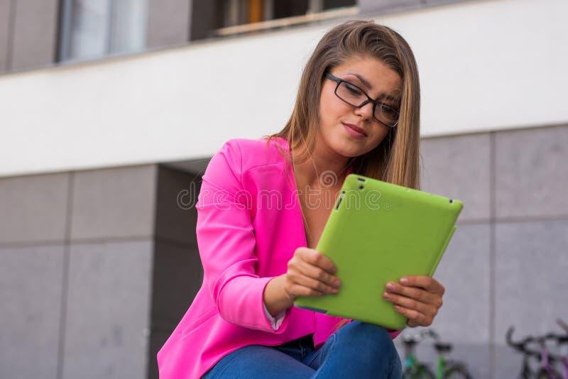 年轻美丽的女实业家坐与绿色tabl的一条长凳 库存图片