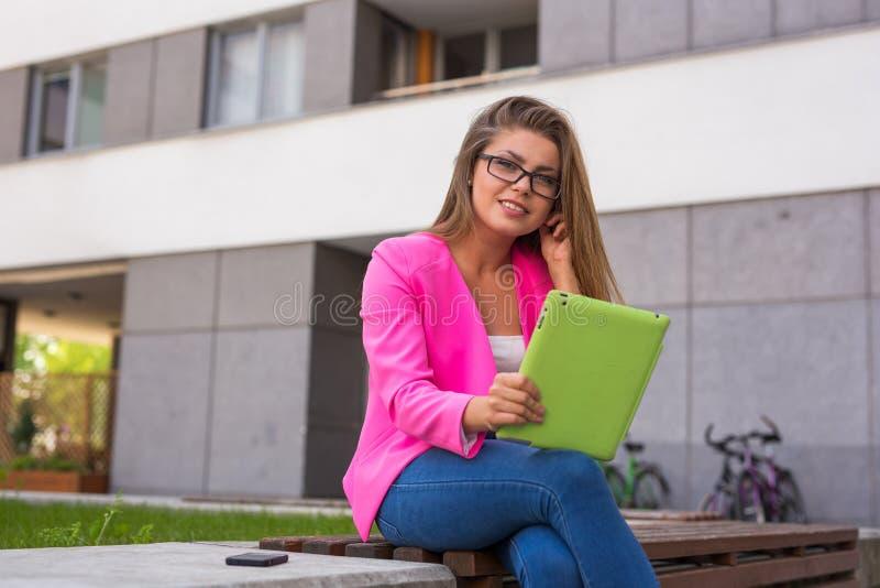 年轻美丽的女实业家坐与绿色tabl的一条长凳 库存照片