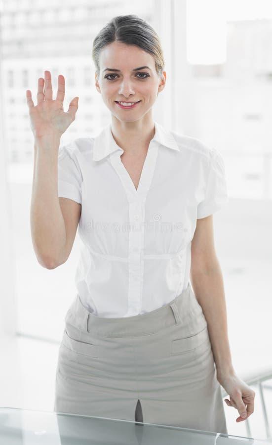 美丽的女实业家挥动的站立在她的办公室 库存照片