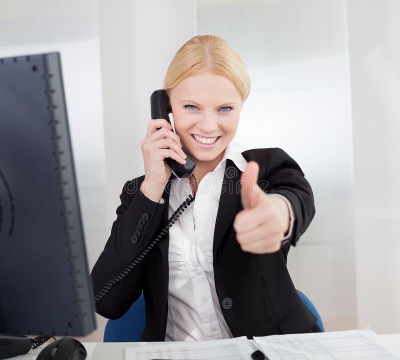 美丽的女实业家联系在电话 免版税库存图片