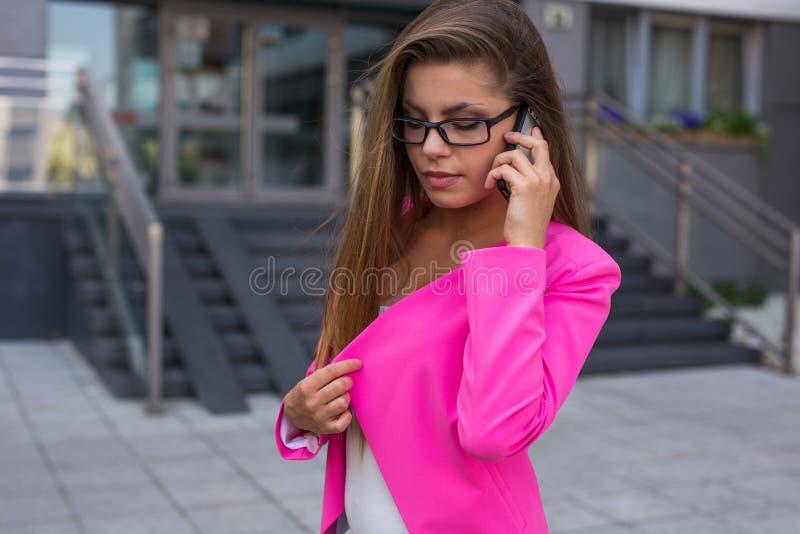 年轻美丽的女实业家谈话在她的与cli的smathphone 免版税库存图片