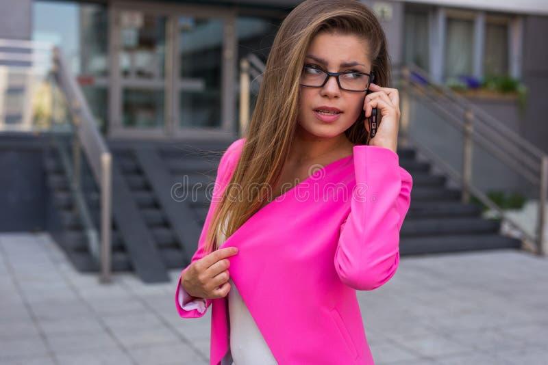 年轻美丽的女实业家谈话在她的与cli的smathphone 免版税图库摄影