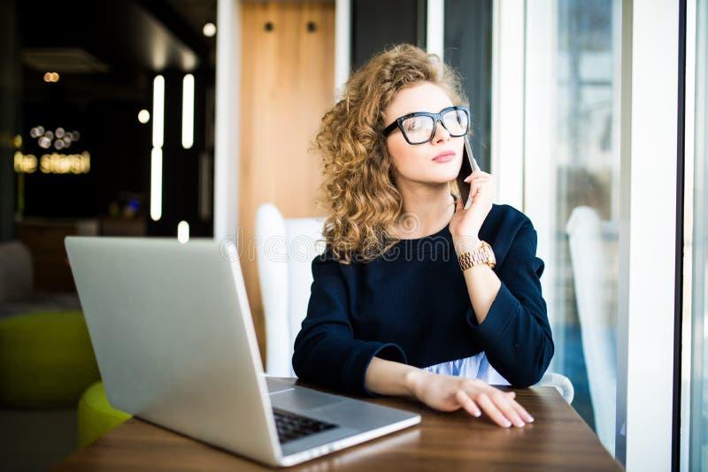 美丽的女实业家运作的坐在她的书桌在办公室 看在窗口 免版税库存照片