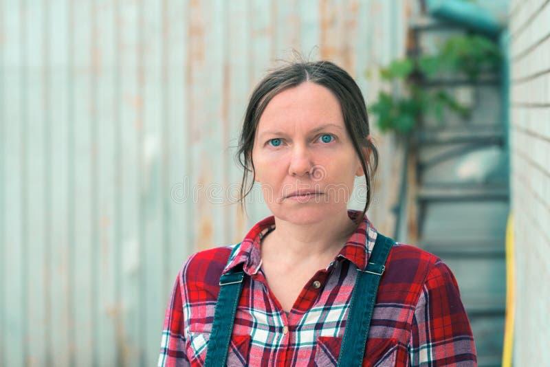 美丽的女性农夫画象在农舍棚子前面的 免版税库存照片