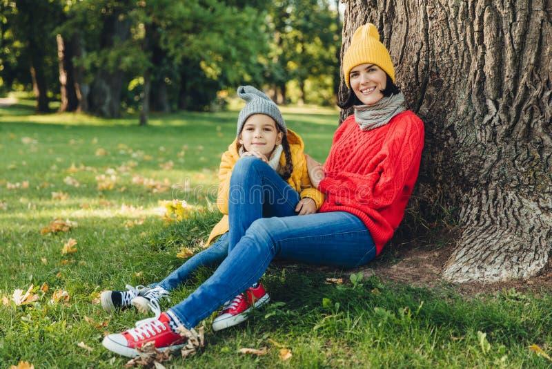 美丽的女性室外画象在温暖的盖帽穿戴了,并且温暖的宽松毛线衣与她的小女儿一起度过周末, 库存图片