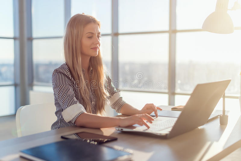 年轻美丽的女性撰稿人键入的文本和博克在宽敞轻的办公室,她的工作场所,使用个人计算机键盘 免版税库存照片