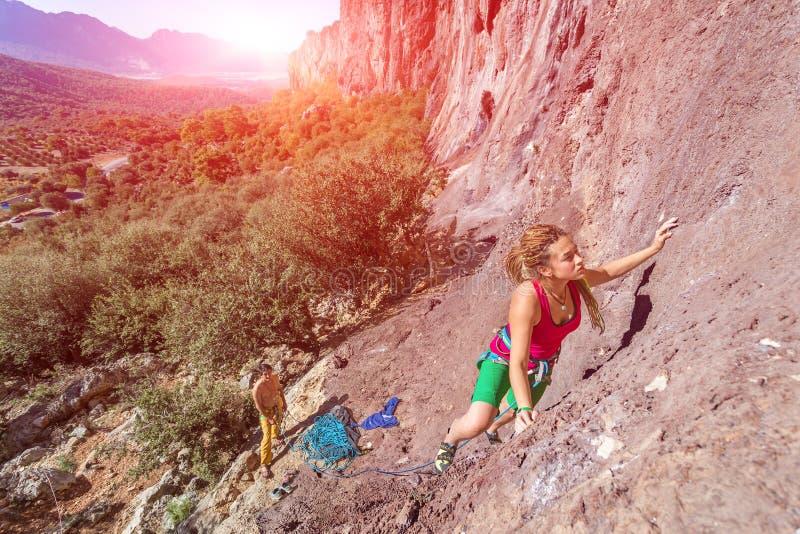 年轻美丽的女性攀岩运动员上升的岩石墙壁 库存照片
