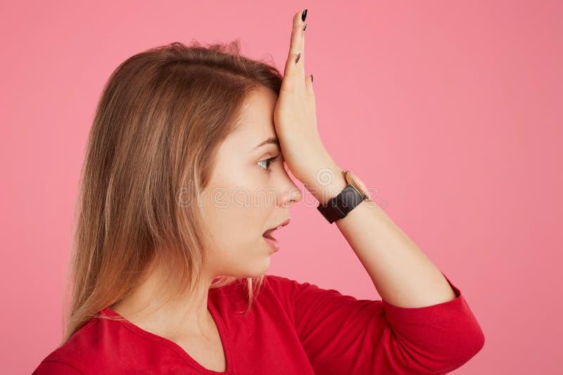 美丽的女性斜向一边的画象保留在前额的手,记住做重要的事,展示她的坏记忆, lo 免版税库存照片