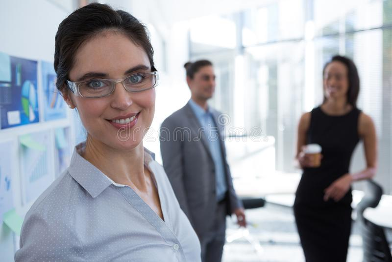美丽的女性看照相机的执行委员佩带的眼镜 库存图片