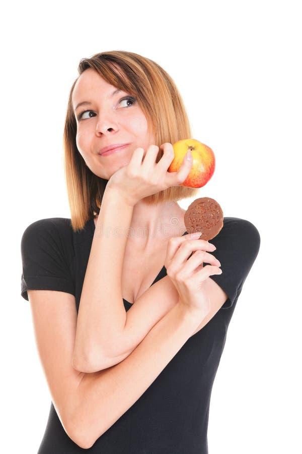 年轻美丽的女性从甜蛋糕和红色苹果选择 库存图片