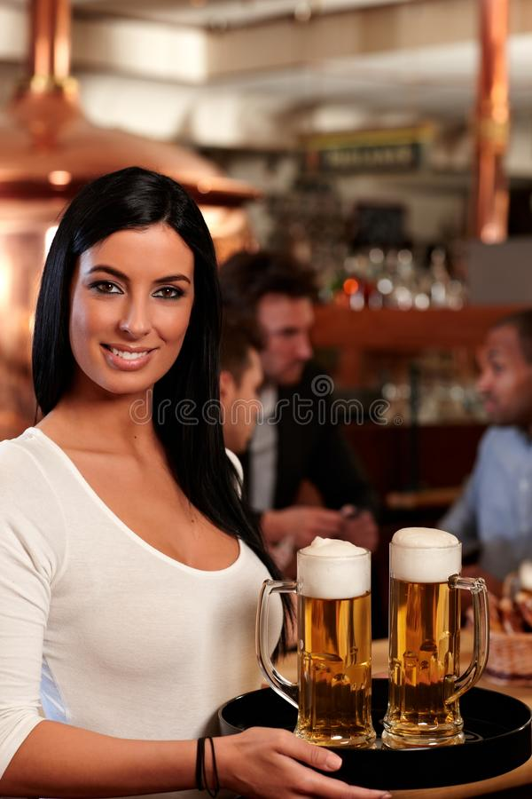 美丽的女服务员服务啤酒 免版税库存图片