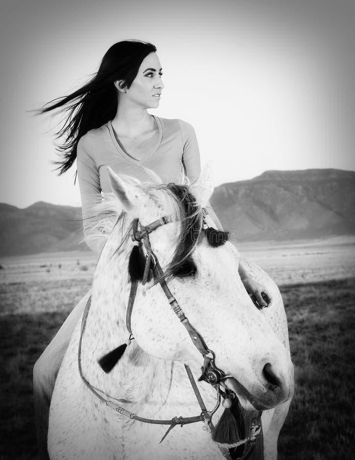 美丽的女牛仔起斑纹马骑术白色 免版税库存照片
