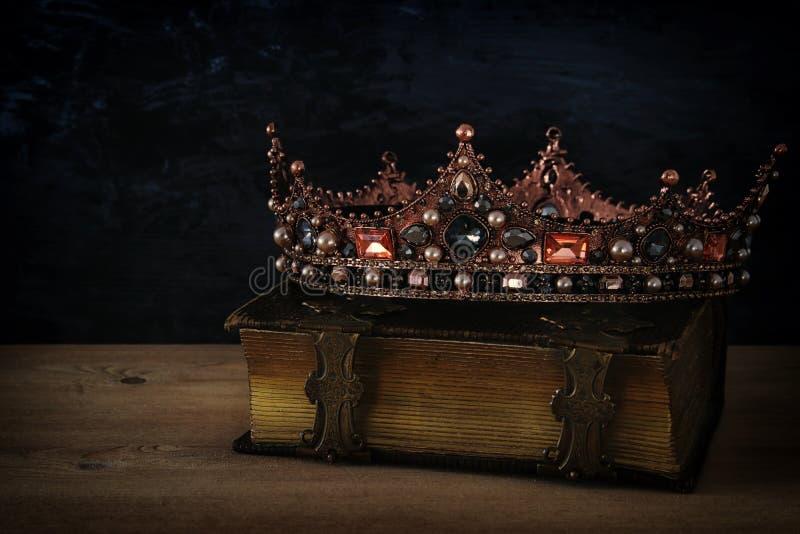 美丽的女王/王后/国王冠的低调图象在旧书 免版税库存照片