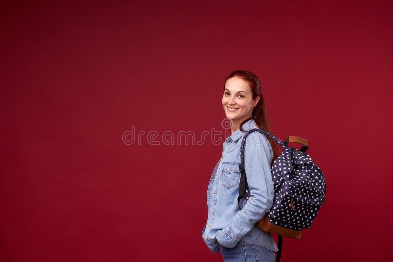 美丽的女生 牛仔裤和一个背包的一名正面红发学生在她的在红色背景立场的肩膀后和 免版税库存图片