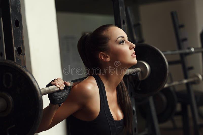 美丽的女运动员蹲与杠铃 免版税库存照片