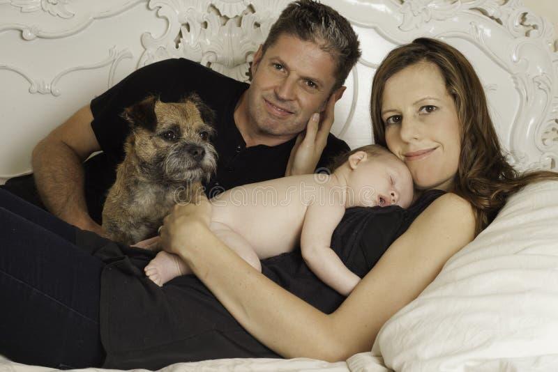 美丽的妇女、她的丈夫、新出生的婴孩和狗 免版税库存照片