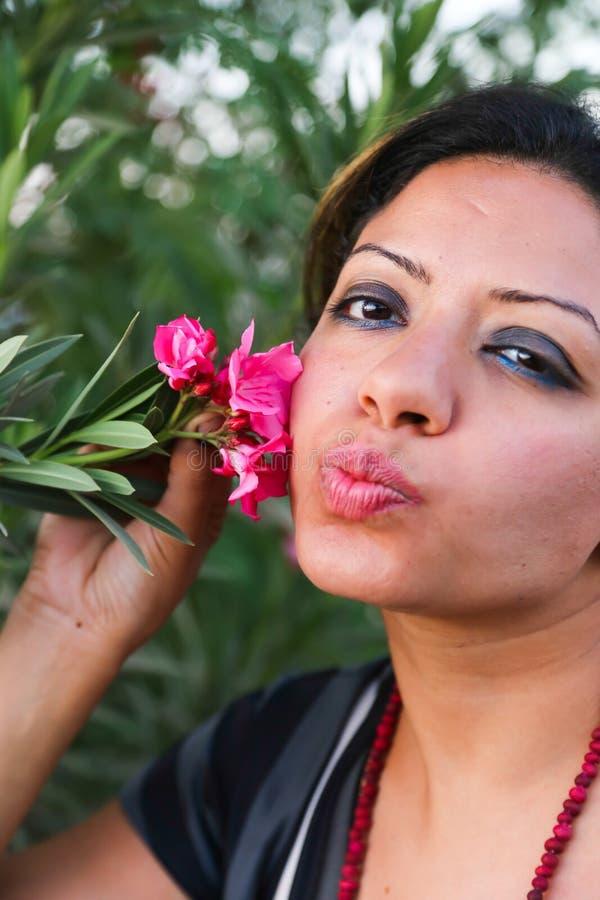 美丽的妇女亲吻花 免版税库存图片