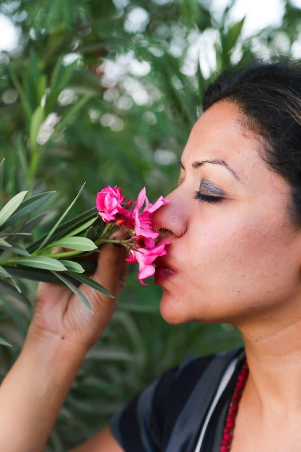 美丽的妇女亲吻花 免版税库存照片