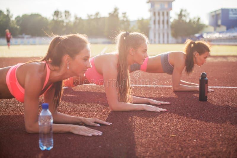 年轻美丽的妇女侧视图做板条的运动服的 免版税库存照片