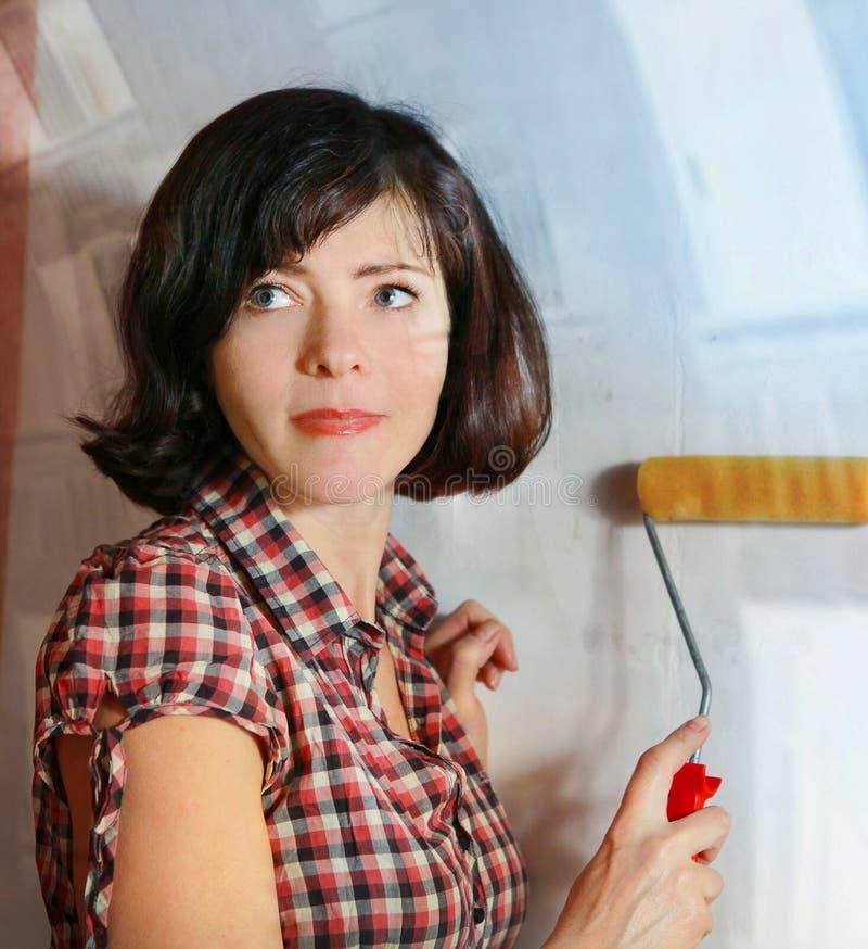 美丽的妇女做一repairment准备垂悬墙纸 库存照片