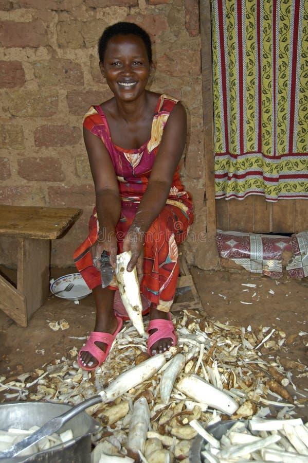 美丽的妇女切开在她的房子前面的糖芦苇 免版税图库摄影