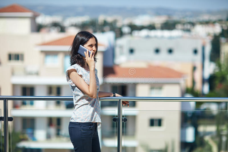 美丽的妇女发表演讲关于在屋顶的手机 免版税库存图片