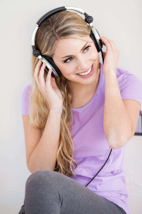 年轻美丽的妇女听与耳机的音乐 库存照片