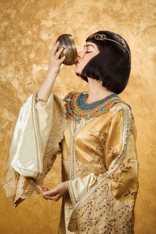 美丽的妇女喜欢埃及女王喝从在金黄背景的杯子的帕特拉 库存图片