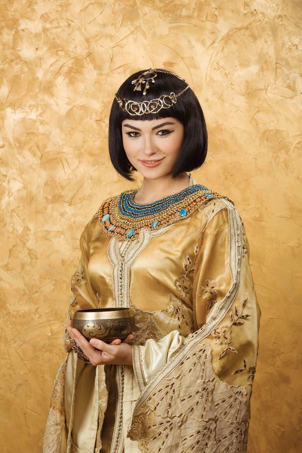 美丽的妇女喜欢有杯子的埃及女王帕特拉在金黄背景 库存图片