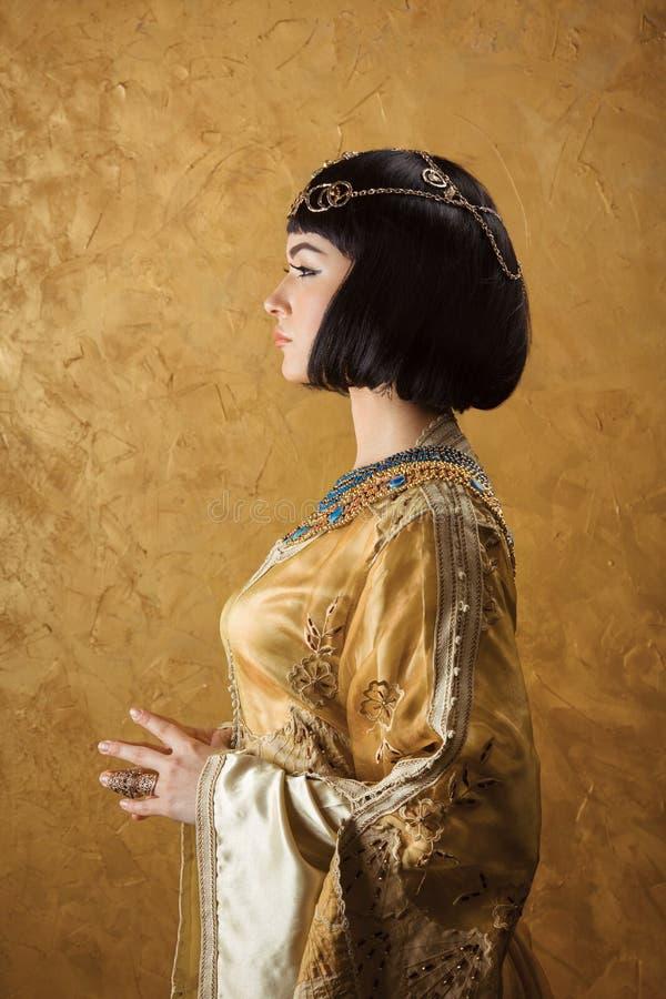 美丽的妇女喜欢金黄背景的埃及女王帕特拉 侧视图,面孔外形 免版税库存照片