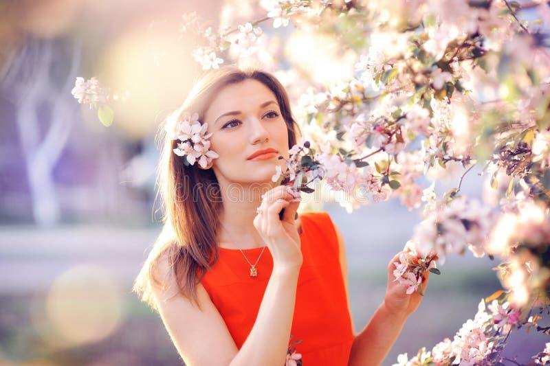 美丽的妇女在一个繁茂花园里在春天 库存图片