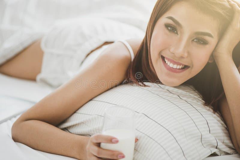美丽的妇女在与一个杯子的床上牛奶 图库摄影