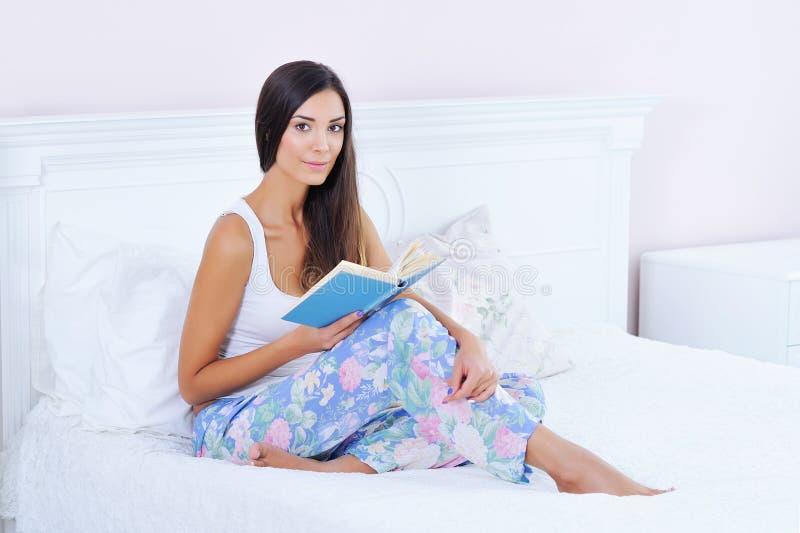 美丽的妇女在床上的读一本书 免版税库存图片