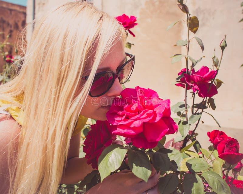 美丽的妇女在庭院里嗅芬芳英国兰开斯特家族族徽 免版税库存照片