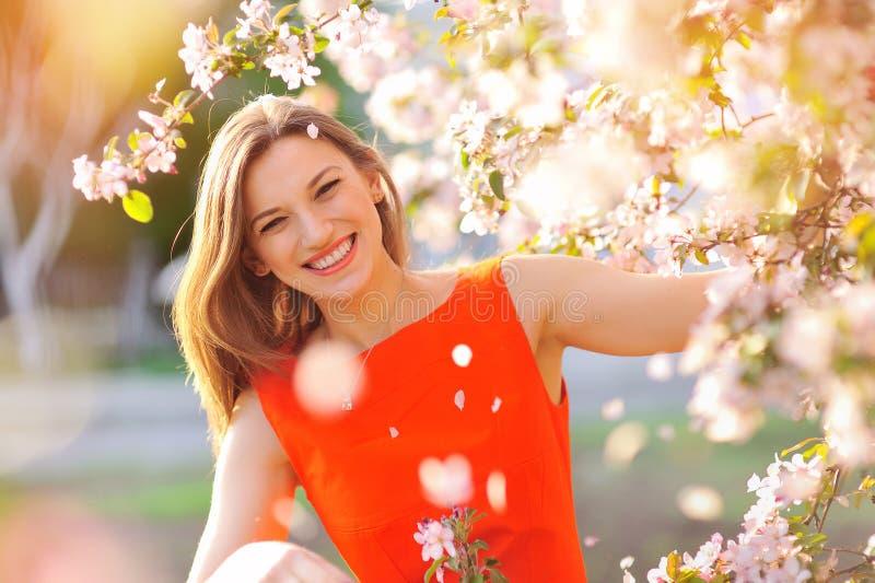 年轻美丽的妇女在开花的庭院里 库存照片
