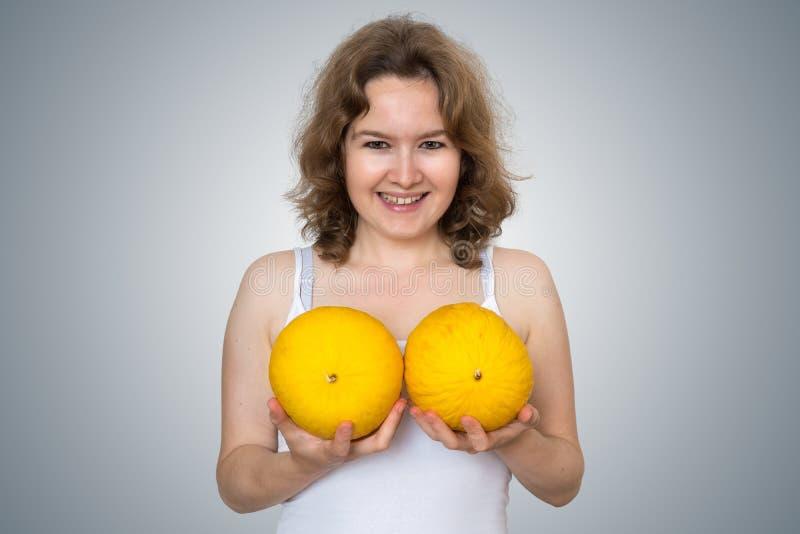年轻美丽的妇女在手上拿着瓜在她的乳房整容手术上,并且硅树脂种入概念 图库摄影