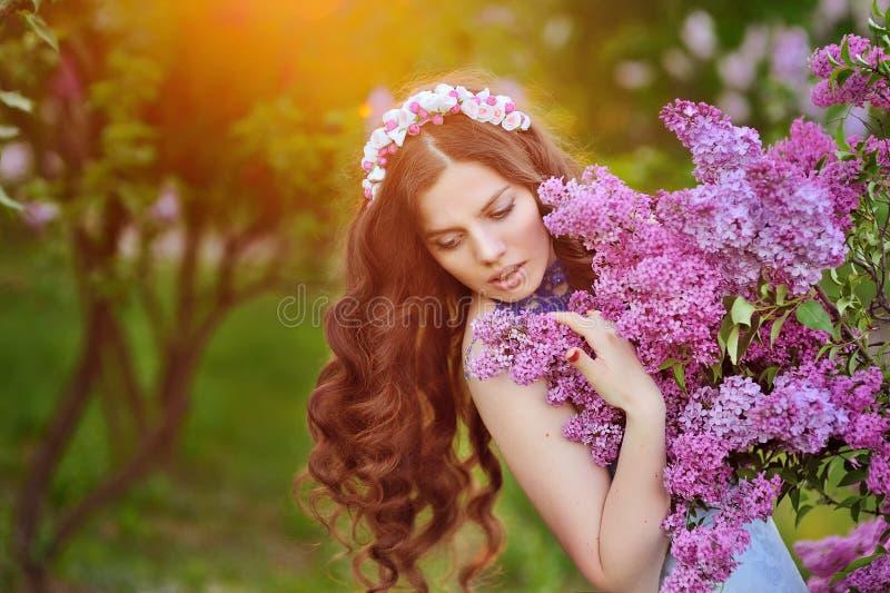 美丽的妇女在春天公园和落日 免版税库存照片