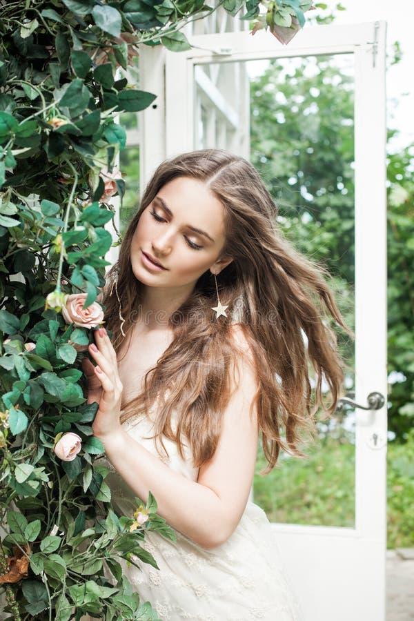 美丽的妇女在春天户外玫瑰园里 免版税库存图片