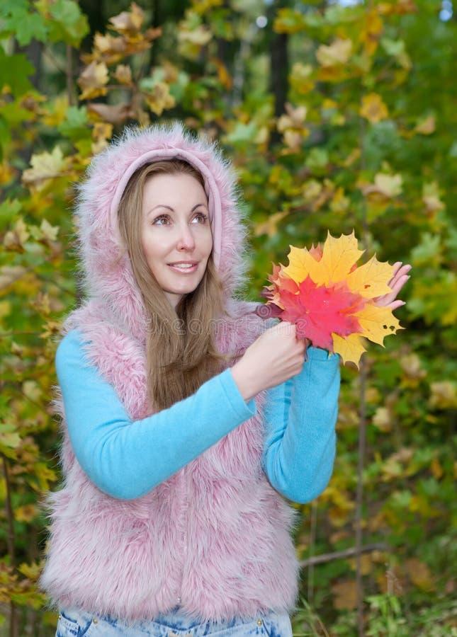 美丽的妇女在有一一抱的秋天公园槭树离开 免版税库存图片