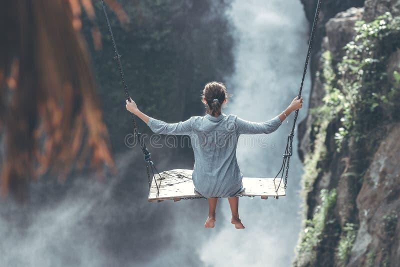 美丽的妇女在瀑布附近摇摆在巴厘岛,印度尼西亚密林  免版税库存图片