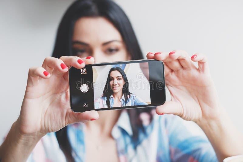 美丽的妇女在电话拍照片的自己 库存图片
